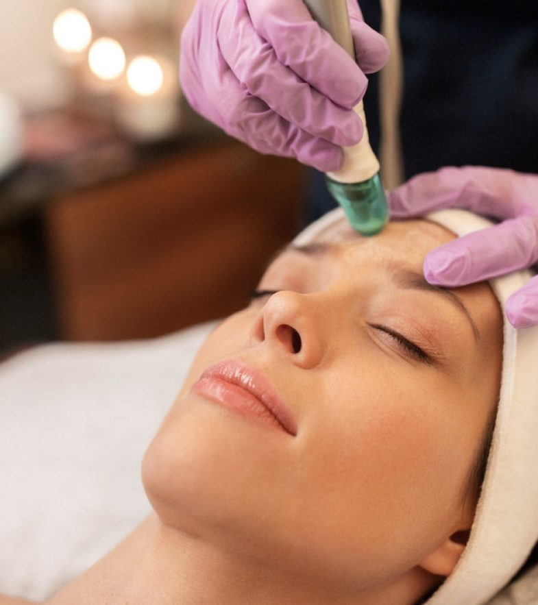 people, beauty, cosmetology, exfoliation and technology concept - beautiful young woman having microdermabrasion facial treatment with crystals in spa