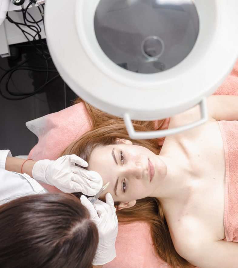 Woman having botox treatment at Beauty clinic. Top view